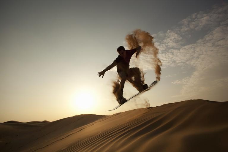 man sand boarding in desert