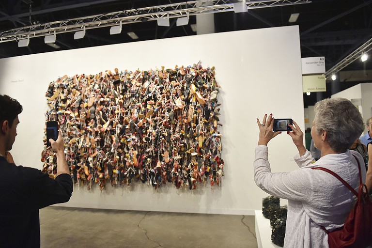 Attendees view 'Ladies and Gentlemen' by artist Hassan Sharif at the Art Basel Miami Beach - VIP Preview at the Miami Beach Convention Center