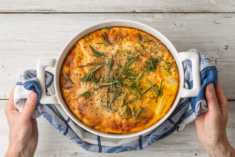Moussaka with rosemary in ceramic pan in hand top view