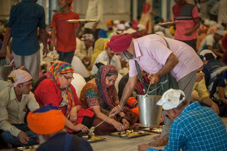 Sikh volunteer offers extra food to people in Gurudwara Bangla Sahib, feeding as many as 25,000 - 40,000 people in a day