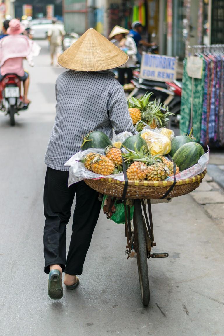 Vietnamese woman street vendor selling street fruits, Hanoi, Vietnam.