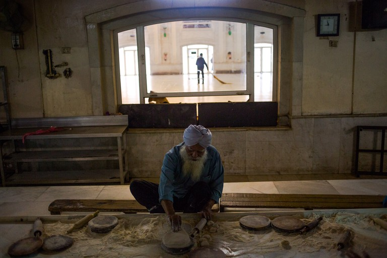 A volunteer makes roti to be served as part of a communal meal, as another sweeps the hall where meals are served, at the Bangla Sahib gurudwara
