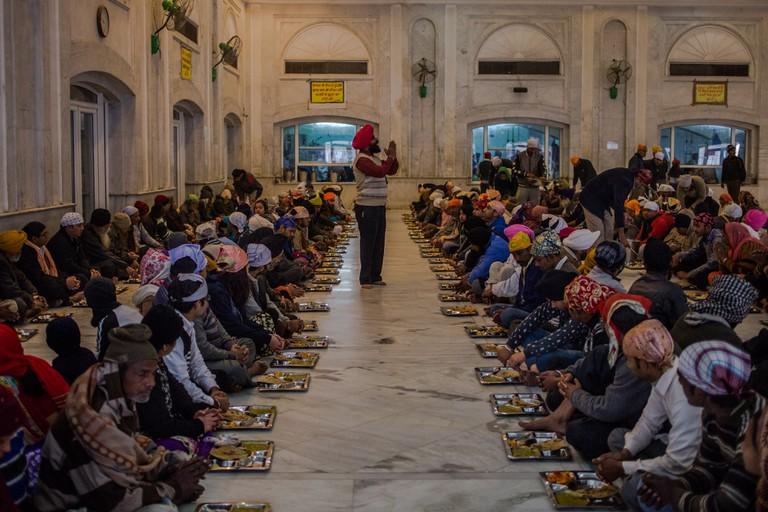 An Indian Sikh volunteer recites a prayer as devotees gather to receive a free communal meal at the Bangla Sahib gurudwara
