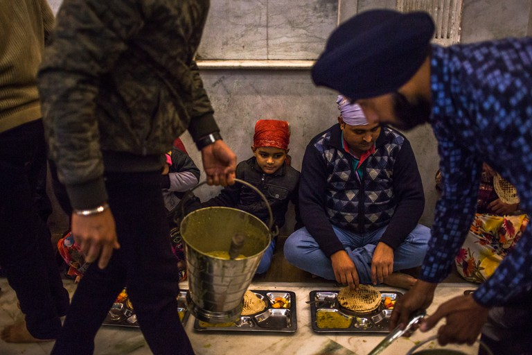 Indian Sikh volunteers serve a free communal meal to devotees at the Bangla Sahib gurudwara