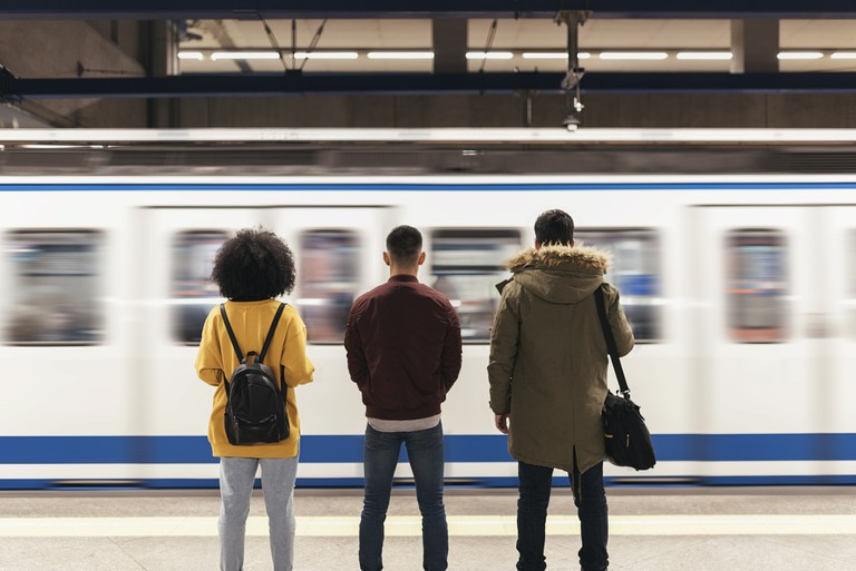 Group of friends waiting the train in the platform of subway station.