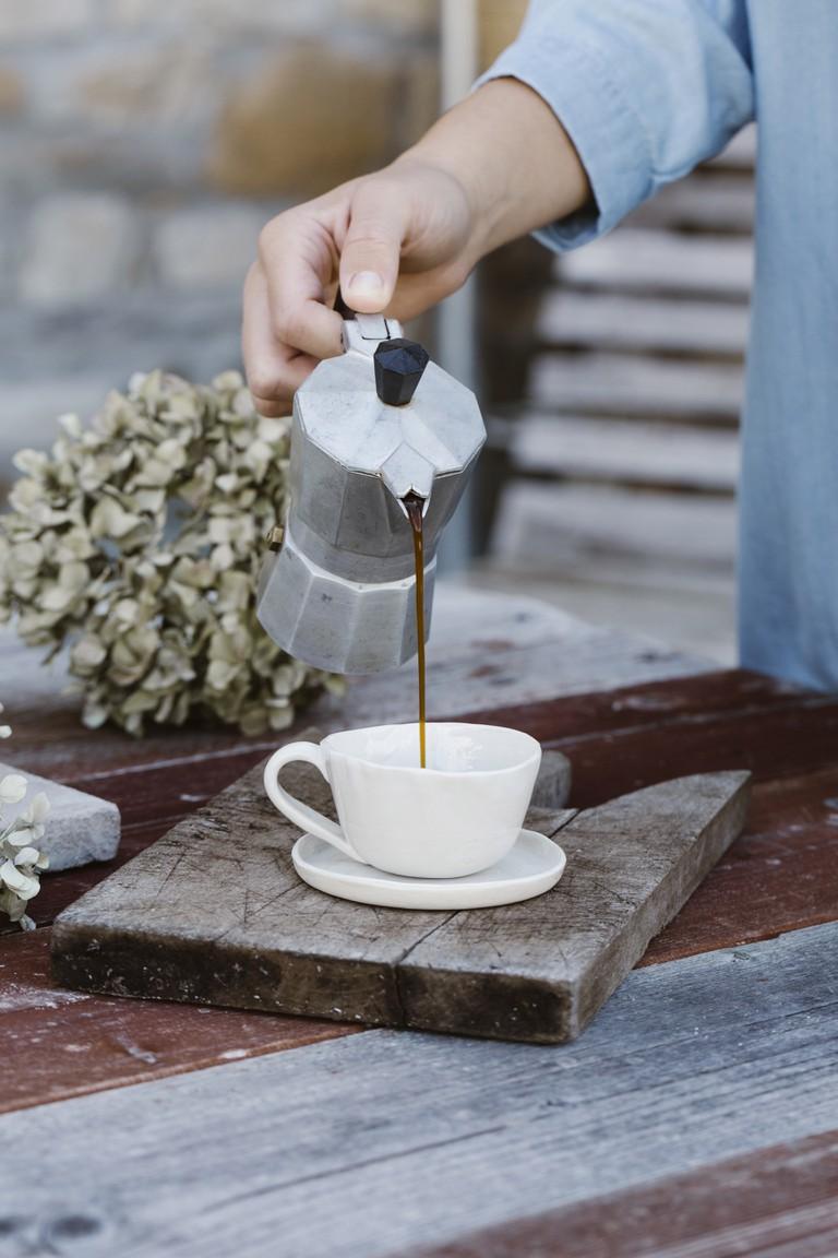 Italian woman pouring espresso