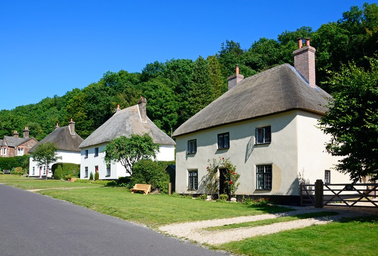 View along the pretty village street with thatched cottages, Milton Abbas, Dorset, England, UK, Western Europe.