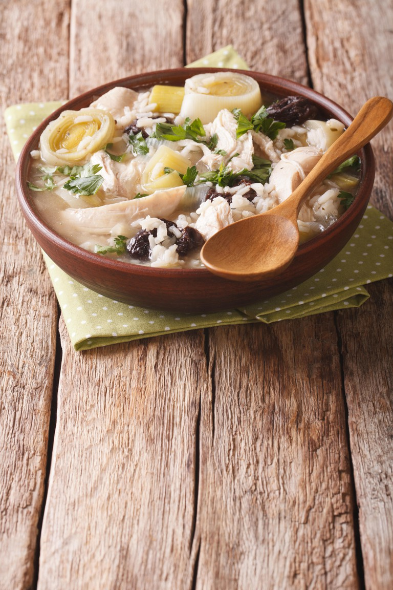 Festive Scottish chicken soup with leeks and prunes close up in a bowl on the table. vertical