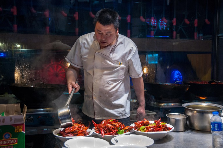 A chef plates up bowls of freshly fried crayfish (yabbies) on Shanghai's Shouning Road food street.