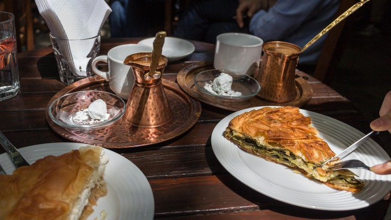 Hand cutting a portion of spanakopita, a greek traditional spinach pie on a table with copper pot with coffee, outdoors.