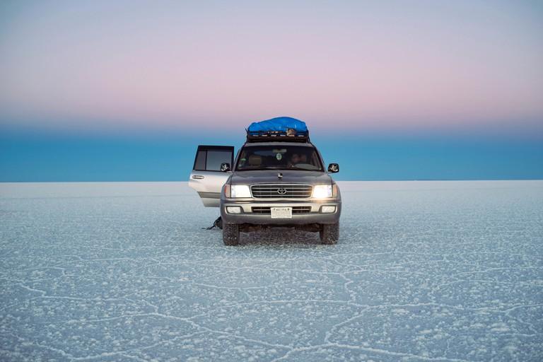 Land Cruiser during twilight in Uyuni salt flats (Salar de Uyuni) Bolivia, South America. Jun 2018