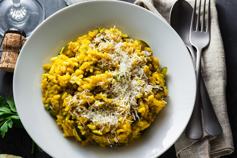 Italian dish yellow Risotto milanese with saffron, zucchini and Parmesan cheese on a black slate table with white wine in a glass. north Italy kitchen
