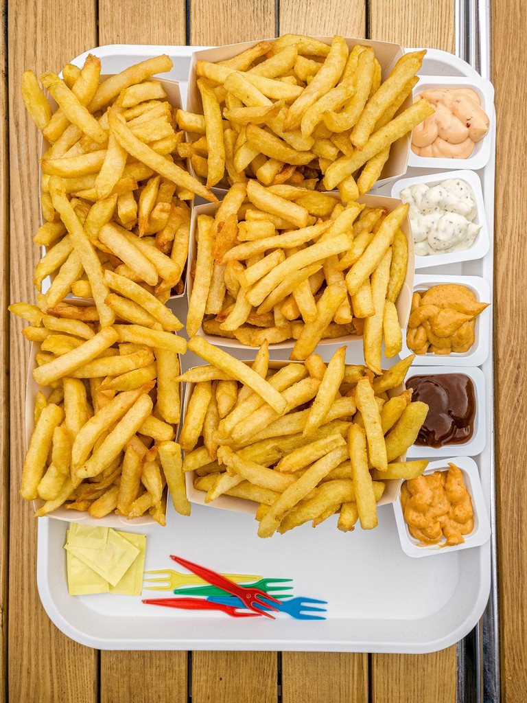 Five servings Belgian fries with five different sauces, plastic forks and salt packets on a white plastic tray on a wooden table.