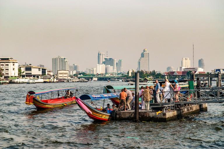 Tourists embarking on river tour boats, Chao Phraya River, Bangkok, Thailand
