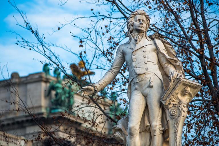 Mozart statue at Neue Burg building part of the Hofburg palace complex seen from Burggarten. Vienna, Austria.