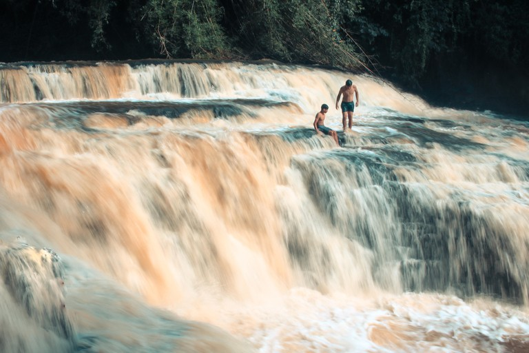 two children playing in a waterfall in nature
