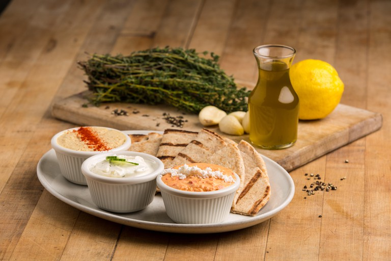 greek appetizers with olives and dips served on white plates with pita bread