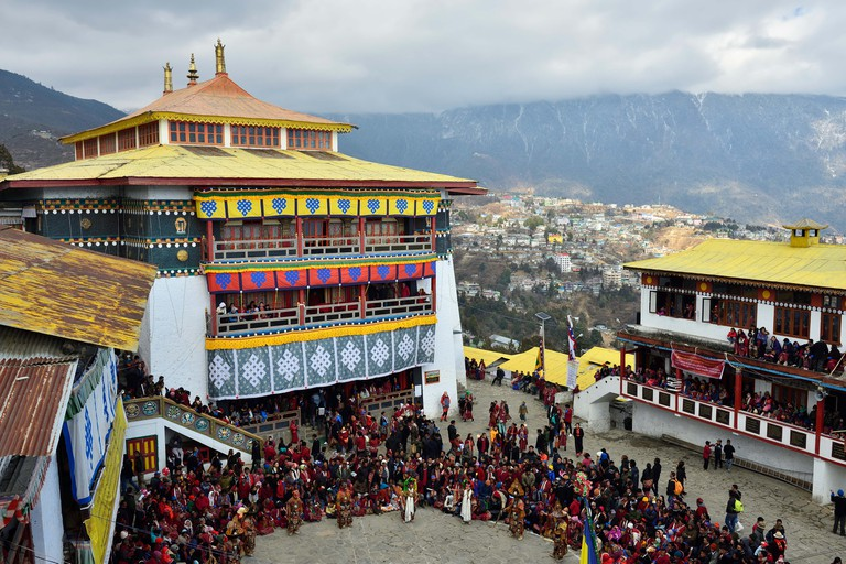 Tawang, Arunachal Pradesh, India, Buddhist monks dancing, Torgya festival, in the background there are monastery and many gathered viewers.
