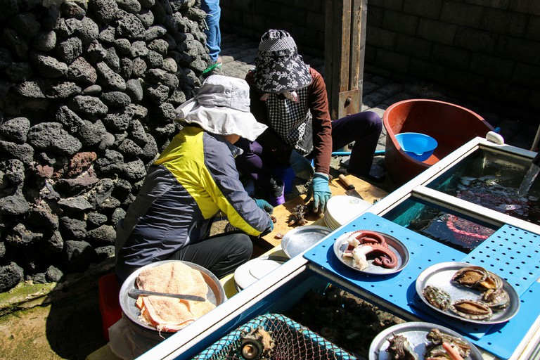 Divers cut a sea catch at Haenyeo Village, Jeju Island, South Korea.