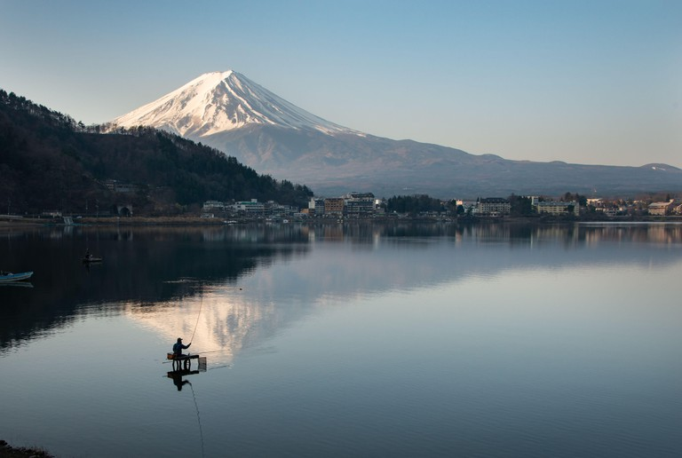 View of Mount Fuji reflected in the lake Kawaguchiko with fishermen out fishing on the lake
