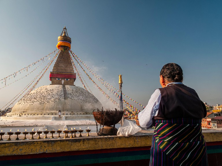 An old woman is performing a religious ceremony at Boudha Stupa