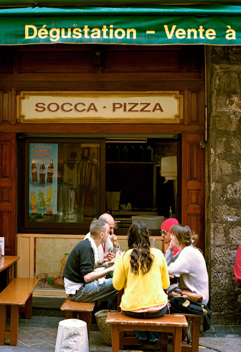 Eating out at a corner shop selling the traditional Nicoise Socca - a chick pea flour pancake in the old town at Nice, France. Image shot 2005. Exact date unknown.