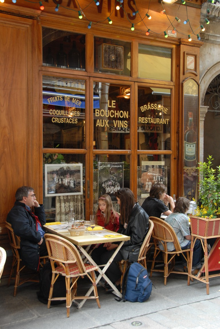 Customers looking at a menu outside a Bouchon restaurant on Rue Merciere in the old town of Lyon, Franc. The long narrow street