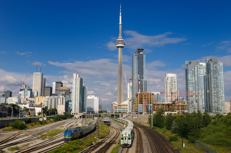 GO and VIA trains leaving downtown Toronto Union Station after work with highrise towers and CN Tower. Image shot 08/2008. Exact date unknown.