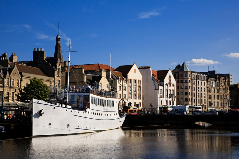 A ship being used as a restaurant moored by the riverside, The Shore, Port of Leith, Edinburgh, Scotland .
