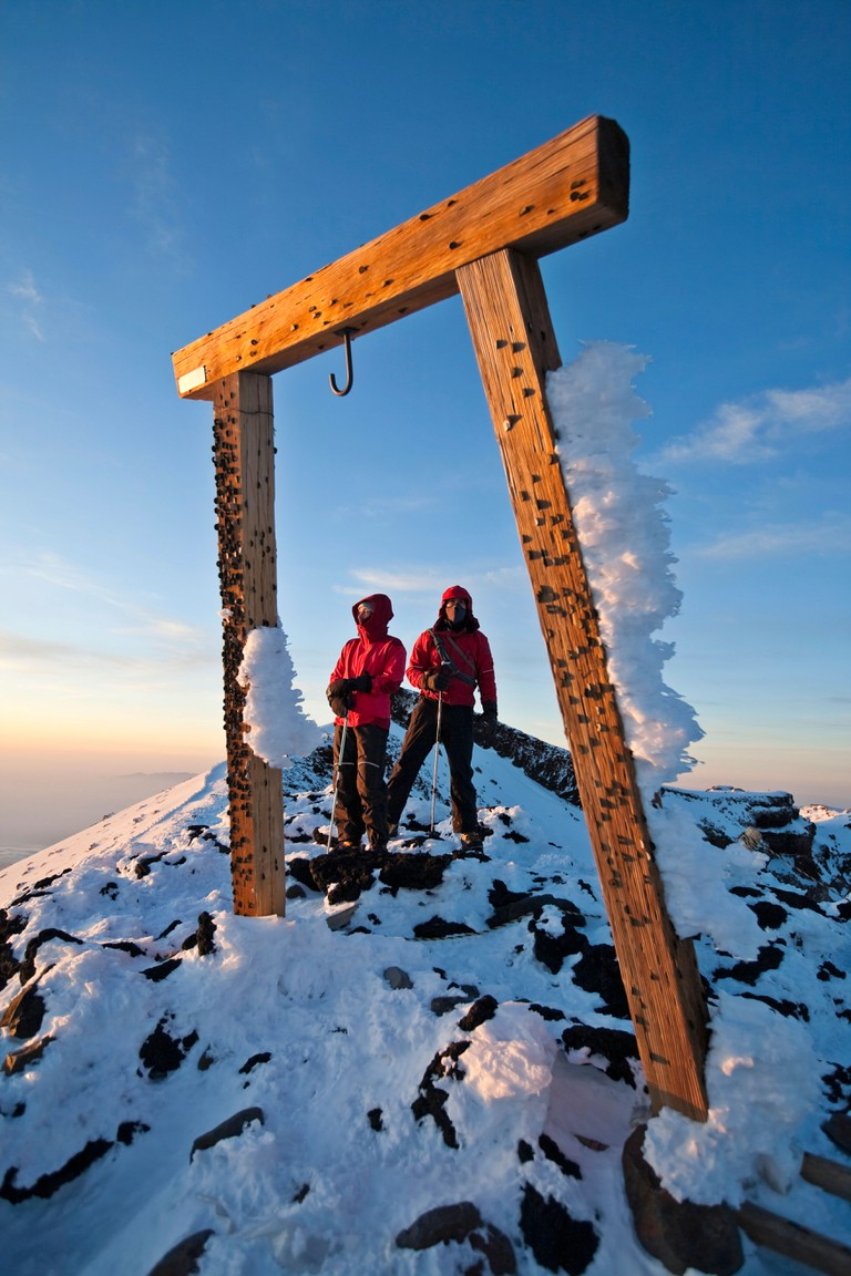 Two people climbing Mount Fuji, Honshu, Japan.