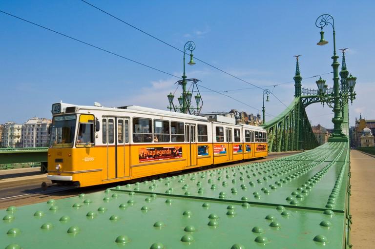 Yellow tram on The Liberty Bridge, Szabadsag hid, over the river Danube, Vamhaz Korut street, Budapest, Hungary, Europe, EU