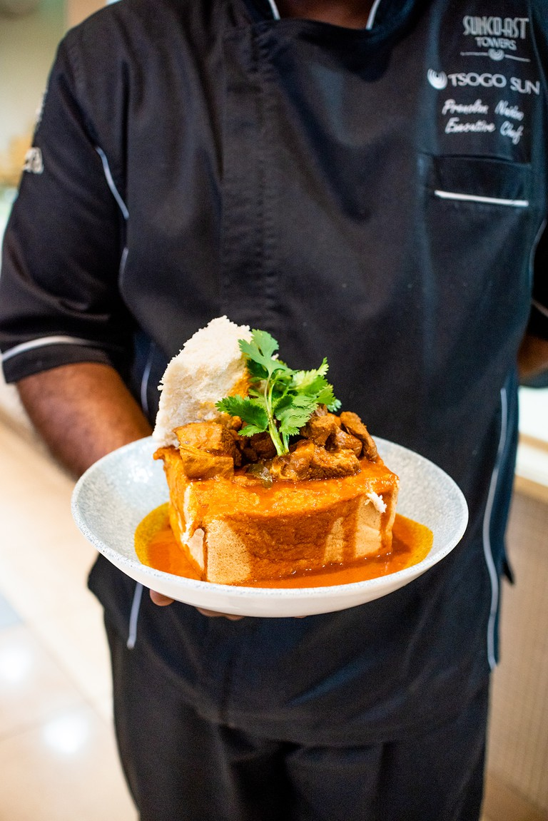Head Chef at Jeera restaurant, Chef Prenolan Naidoo with a plate of his Bunny Chow, Durban, South Africa, 2020