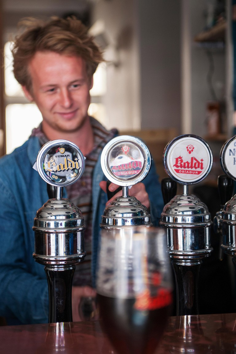 Bartender serving beer from Kaldi micro brew bar in Reykjavik, Iceland.