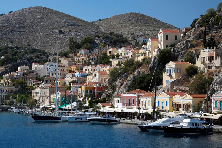 Greece, Dodecanese, Rhodes island, Symi, neoclassical pediments houses are staged on the hills overlooking the sea and harbor