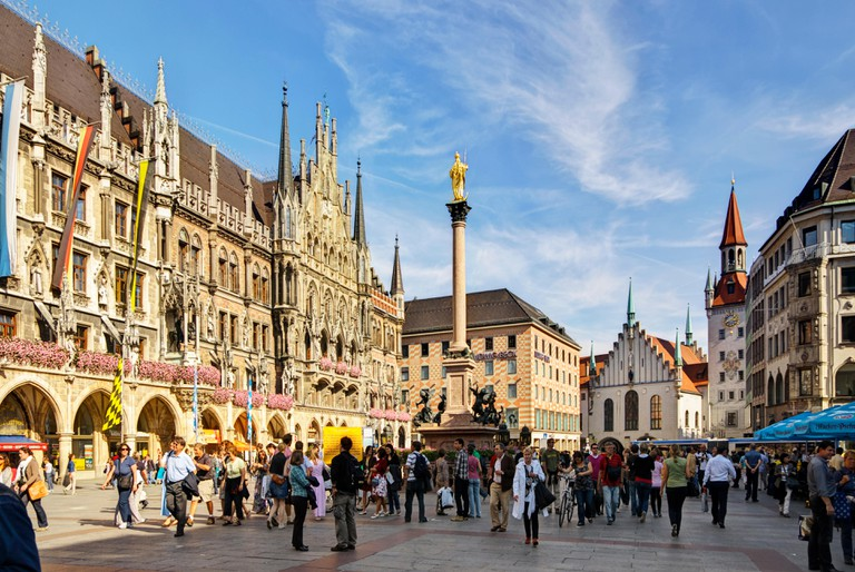Tourists and others walk, shop, eat and drink on the Marienplatz, the central town square in Munchen / Munich, Germany.