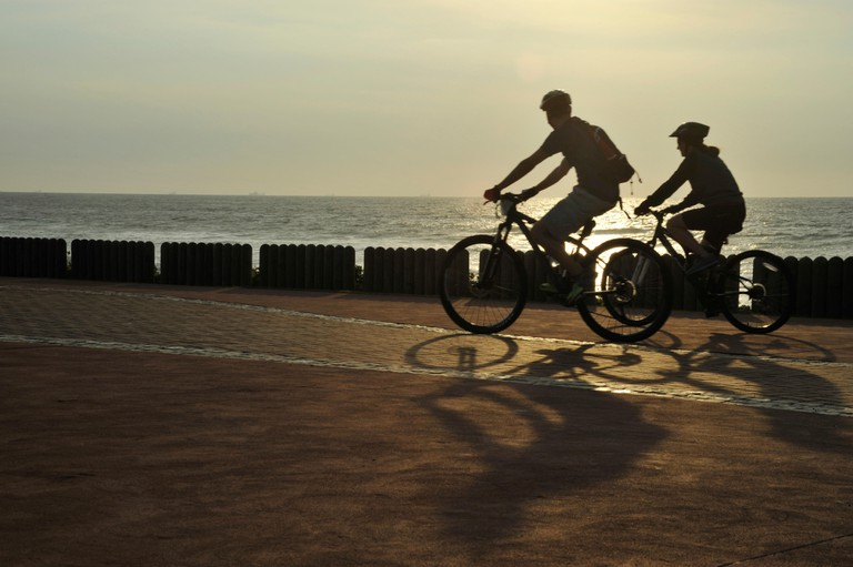 Durban, KwaZulu-Natal, South Africa, silhouette, adult man and woman bicycle riders cycling with mountain bikes on beach, people, landscape