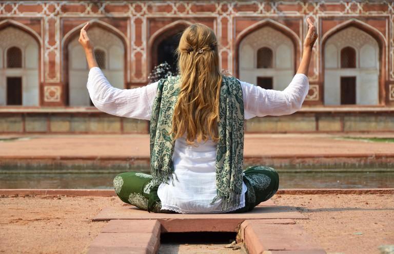 Young woman meditating in the yard of Humayun's Tomb. Delhi