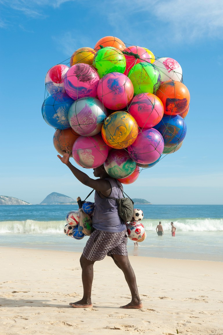 RIO DE JANEIRO, BRAZIL - JANUARY 20, 2013: Beach vendor selling colorful beach balls carries his merchandise along Ipanema Beach
