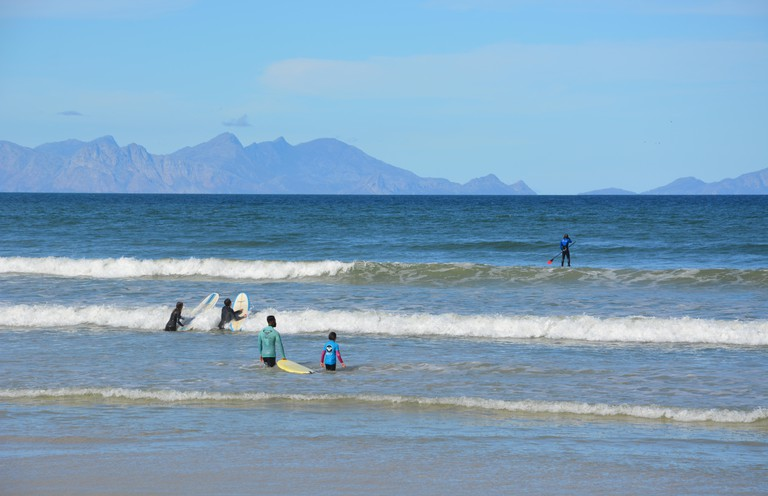Surfers and stand up paddle boarders head out into the water at Surfers Corner
