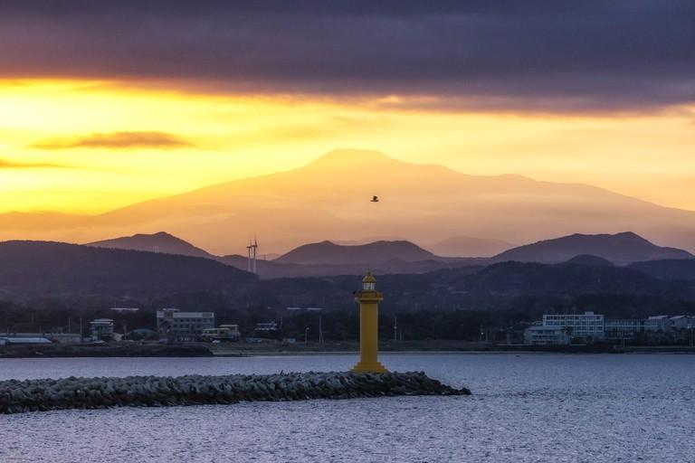 The view of Mount Hallasan with seongsan harbor light house during sunset hours. Jeju Island, South Korea.
