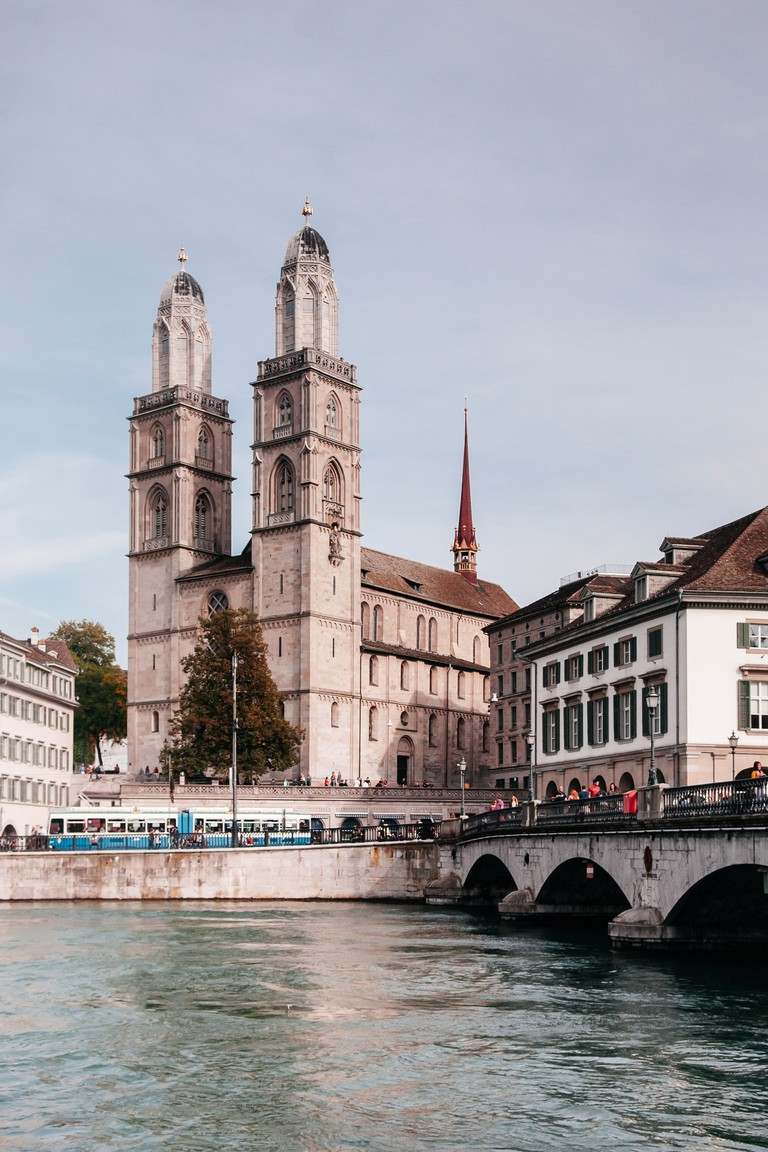 vintage buildings of Grossmunster cathedral and Munsterbrucke over Limmat river in Zurich