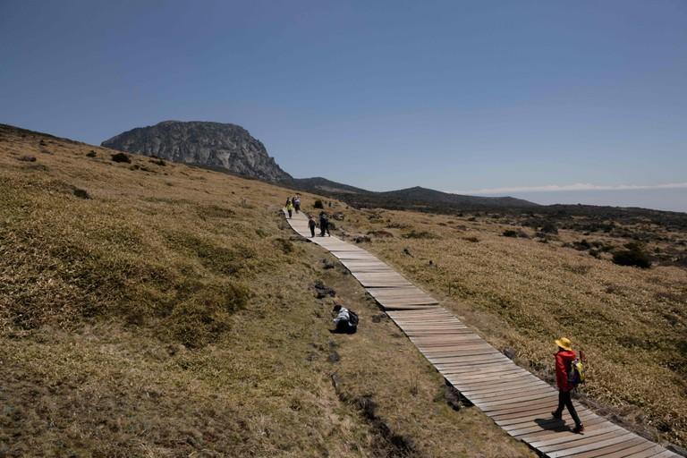 Hikers walking before the peak of Hallasan mountain, on Jeju island.