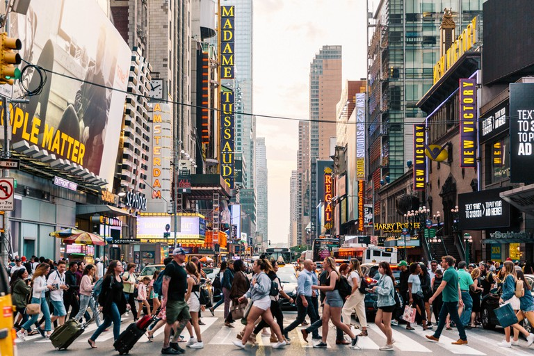 Crowds of people crossing the street in Times Square, New York