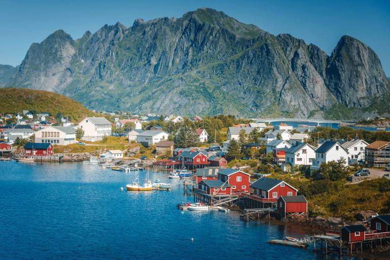 View of the city of Reine on the Lofoten islands, a beautiful bright landscape, white and red houses on a background of rocks at sunset