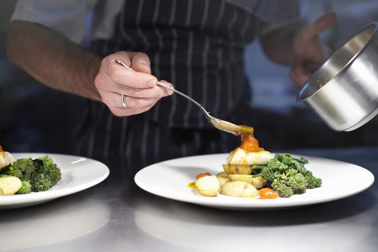 Chef preparing a dish in a restaurant kitchen