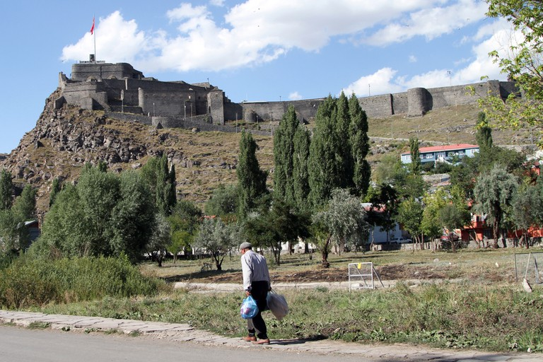 A man walks past Kars Fortress