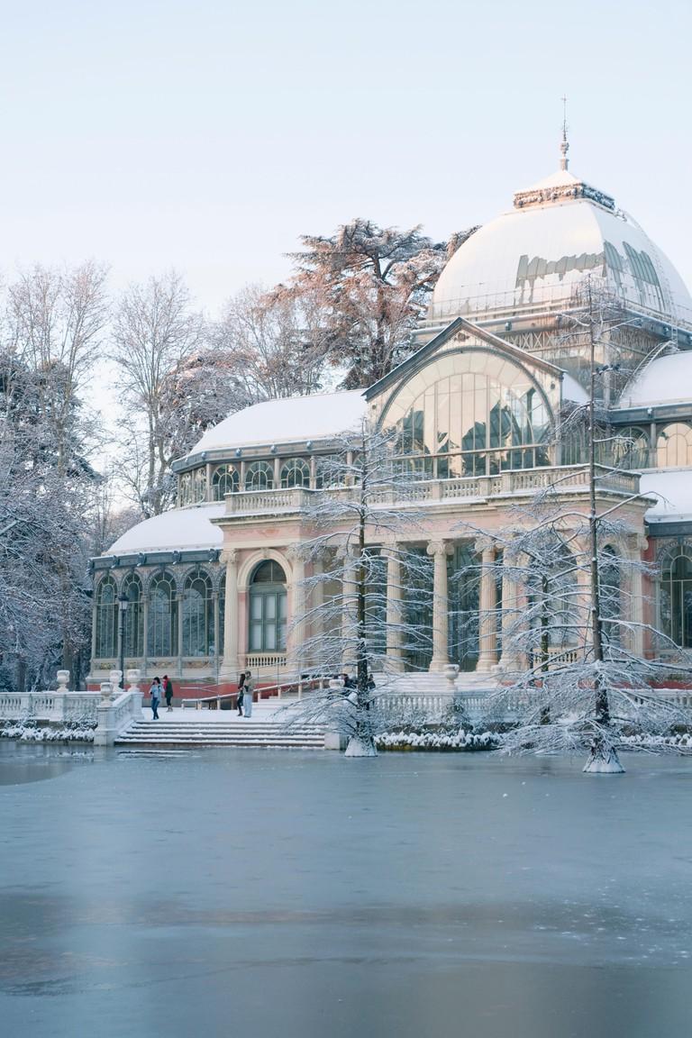 Snow covered Palacio de Cristal. The Retiro park, Madrid, Spain.