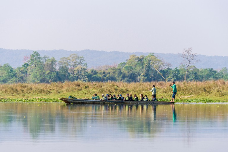 A boat with tourists is floating on the Rapti River in Chitwan National Park