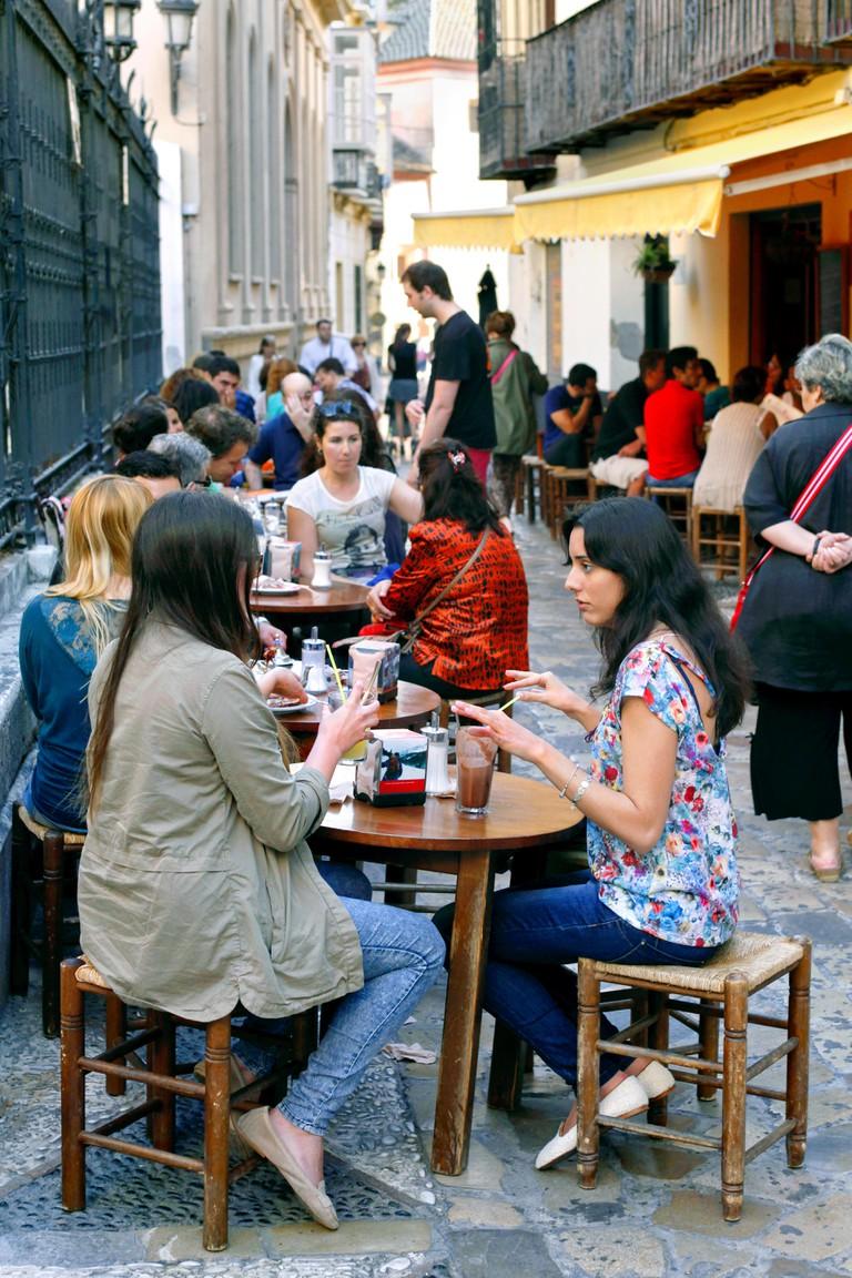 "People sitting outside the popular cafe ""La Teteria"", Calle San Agustin, Malaga."