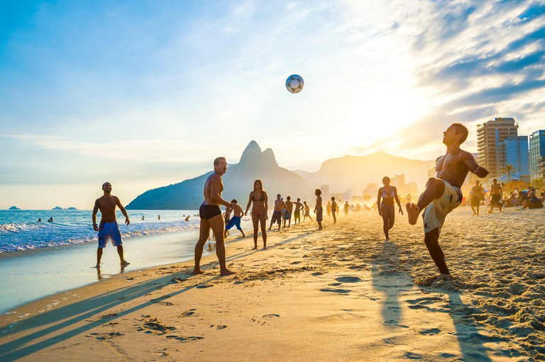 RIO DE JANEIRO - APRIL 01, 2014: Groups of young Brazilians play keepy uppy, or altinho, at sunset on the shore of Ipanema Beach at Posto 9